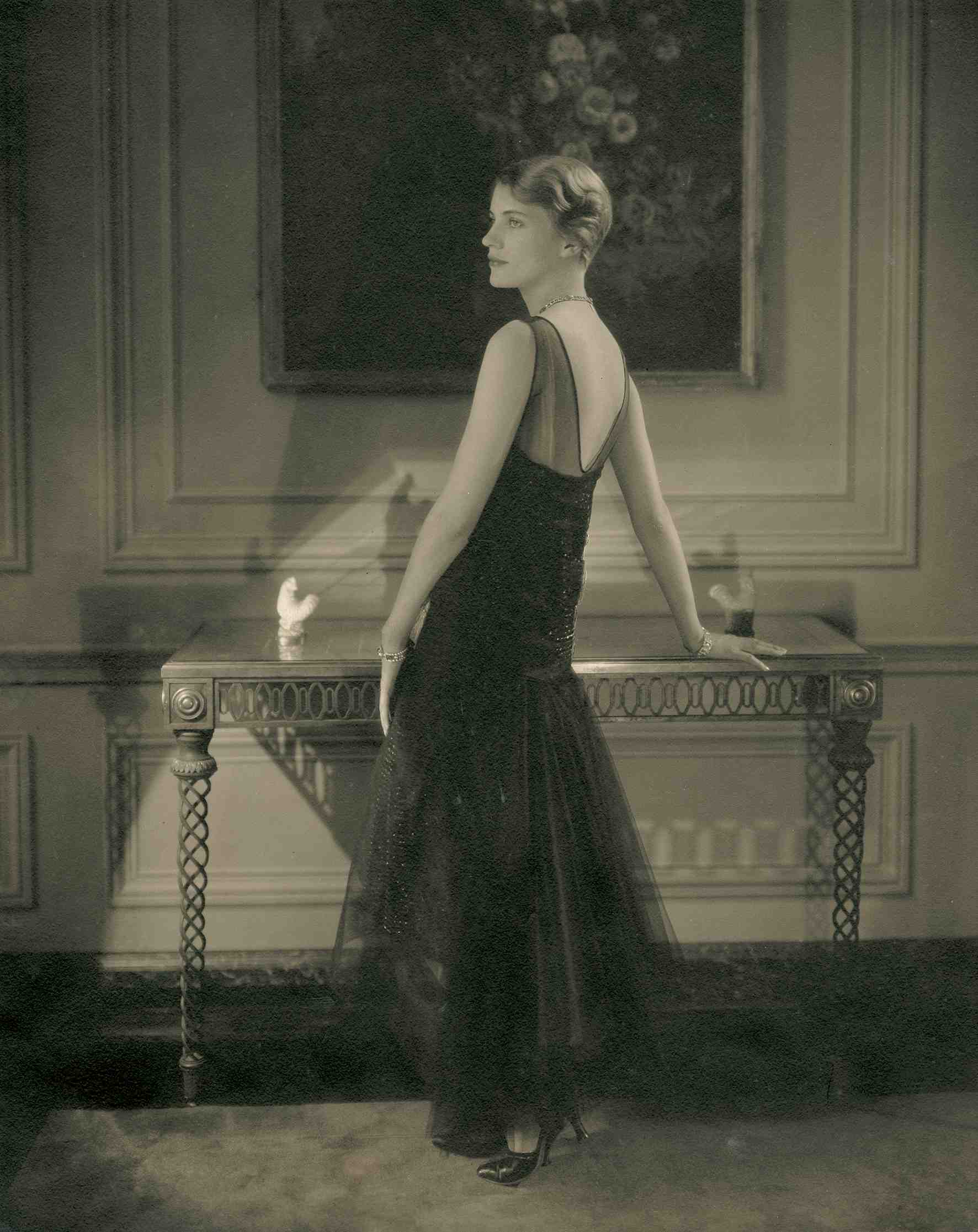 Edward Steichen - Lee Miller wearing a black tulle evening dress by Lelong; black satin pumps by Delman and jewels by Marcus, standing in Condé Nast's apartment, 1928 - Condé Nast Publications, New York