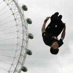 Free-runner Asid demonstrates a free-running move by somersaulting infront of the London Eye in London
