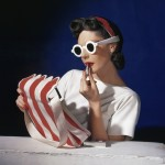 Model Muriel Maxwell in white sunglasses putting on lipstick, wearing red-white-and-blue turban, andv holding a red-and-white striped bag