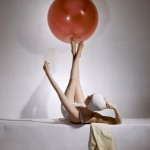 Reclining model in white swimsuit and bathing cap, balancing large red ball on feet