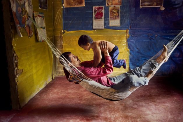 Steve McCurry, A farmer and his son play in a hammock at home, La Esperanza, Colombia, 2004