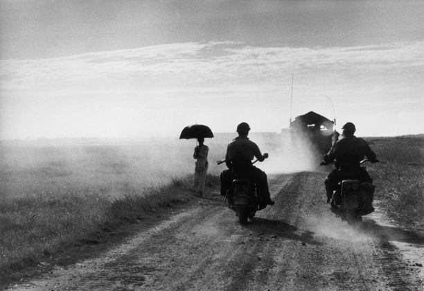 Motociclisti e donna che cammina sulla strada da Nam Dinh a Thai Binh, Vietnam, 25 maggio 1954 © Robert Capa © International Center of Photography-Magnum Photos