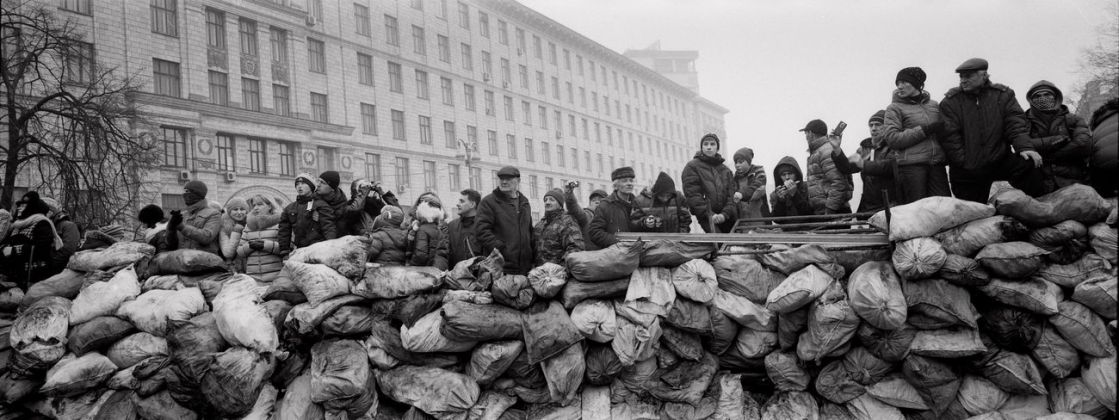 Pavel Wolberg, Ukrainian civilians stand behind a barricade as they watch riot police lines near the Maidan square in Kiev, 2014 © Pavel Wolberg, Prix Pictet 2017