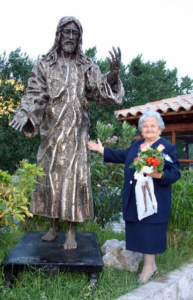 Una fedele in posa accanto a una scultura sacra di Nino Ucchino