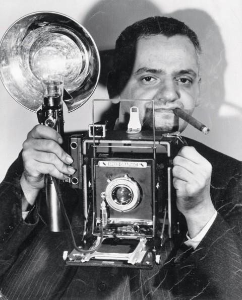 Anonimo, Il fotografo americano di origine polacca Arthur Fellig con la sua macchina fotografica Speed Graphic, dicembre 1943 - Stampa ai sali d'argento, 24,1 x 19,1 cm - New York, International Center of Photography - © Epics / 2010 Getty Images