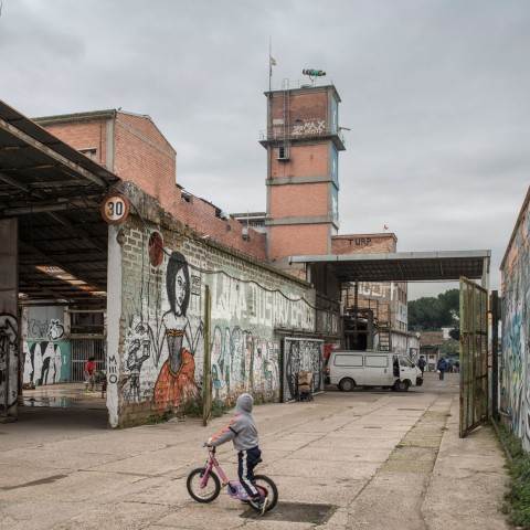 MAAM - Cortile esterno. Un bambino sulla sua bici. Sullo sfondo la torre di Metropoliz con in cima il telescopio di Gian Maria Tosatti - photo Giuliano Ottaviani