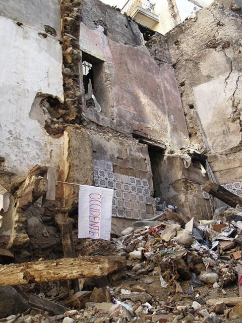 Angelo Bellobono, Caduta d'occidente - azione con bandiera su palazzo crollato nel centro storico di Cosenza