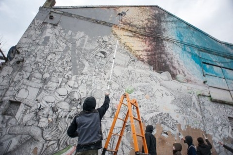 Blu mentre cancella un suo murale a Bologna