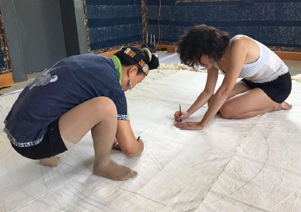 Land Art Mongolia Biennale – Lisa Batacchi – Lavorando insieme con le donne Miao disegnando a matita su tessuto rintracciando le linee dal modello di carta sottostante - photo credits Lisa Batacchi