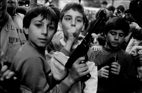 Letizia Battaglia, Festa del giorno dei morti. I bambini giocano con le armi, Palermo, 1986, Courtesy l'artista