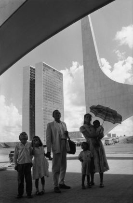 A worker from Nordeste shows his family the new city on inauguration day. In the background the National Congress building by Oscar Niemeyer. Brasilia, Brazil, 1960 © René Burri / Magnum Photos