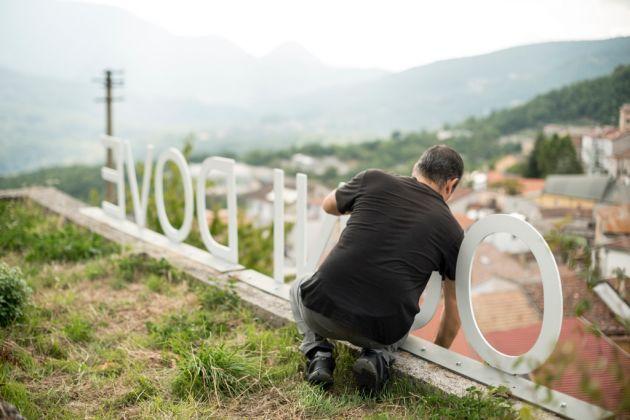Pino Valente ripulisce l'opera Ogni dove (Latronico, 2016) dalle erbe selvatiche – photo Marco Passaro