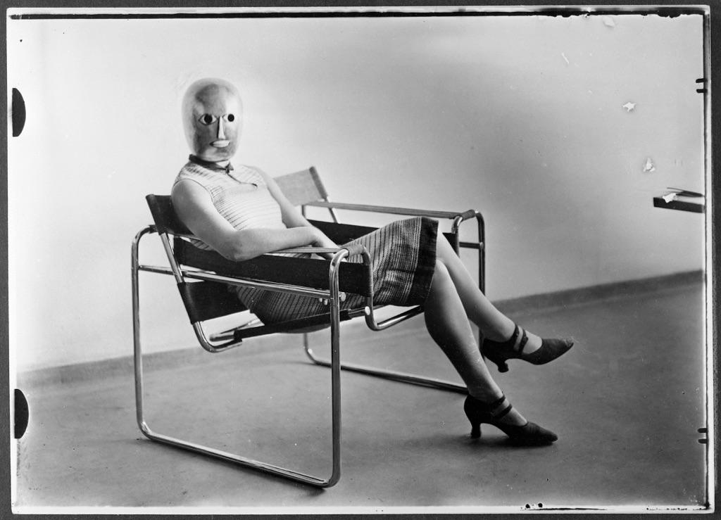 Erich Consemüller, Scena dal Bauhaus. Sconosciuta su una poltrona tubolare di Marcel Breuer con indosso una maschera di Oskar Schlemmer e un abito di Lis Beyer, 1926 © Bauhaus-Archiv Berlin