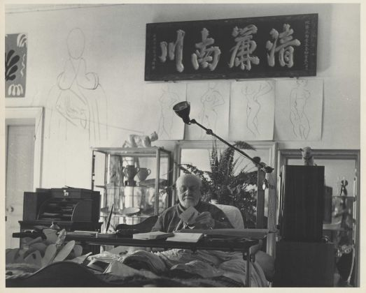 Matisse_MFA_AA. Photograph by Philippe Halsam of Matisse working on a cut-out under his Chinese calligraphy panel