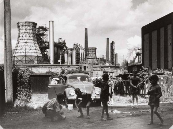 Rudolf Holtappel (Münster, Germania, 1923 – Duisburg, Germania, 2013), Duisburg Bruckhausen, Ebertstrasse con stabilimento metallurgico August Thyssen, 1968, Stampa ai sali d'argento, Estate of the Artist