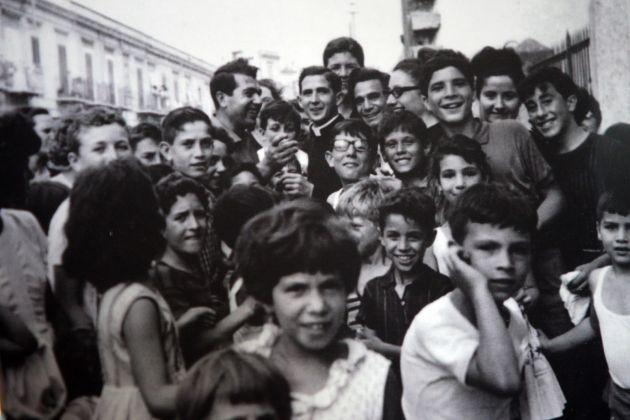 Un giovane Don Pino Puglisi con i ragazzini del quartiere Brancaccio, a Palermo