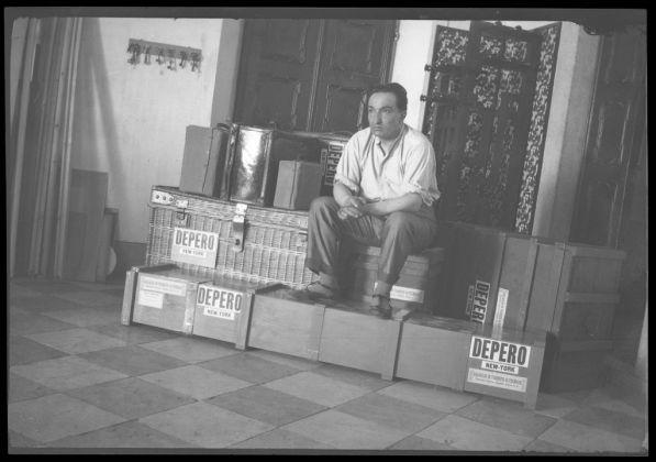 Fortunato Depero seduto sopra le casse dei bagagli attende l'imbarco per New York