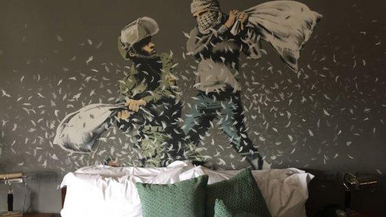 Un palestinese e un israeliano lottano con i cuscini in una stanza del Walled off Hotel, opera di Banksy del 2016