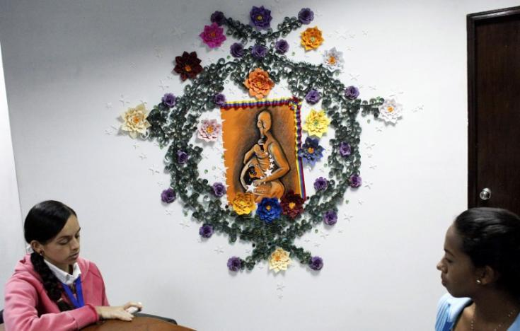 Women speak in front of a painting depicting a pregnant woman wearing a tear gas mask at the Mayor's offices of Barinas, in Barinas