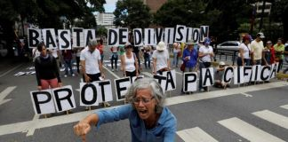 """Opposition supporters shout slogans while hold a banner that reads, """"Stop dividing. Peaceful protest"""", during a rally against Venezuelan President Nicolas Maduro's government in Caracas"""