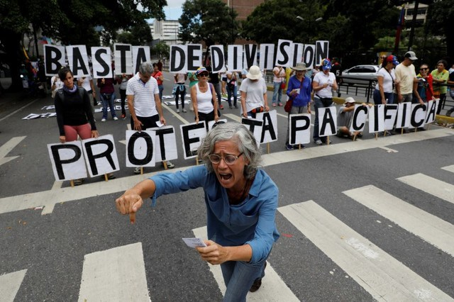 Opposition supporters shout slogans while hold a banner that reads,