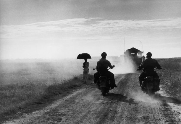Motorcyclists and woman walking on the road from Nam Dinh to Thai Binh, Vietnam, May 25, 1954 © Robert Capa © International Center of PhotographyMagnum Photos