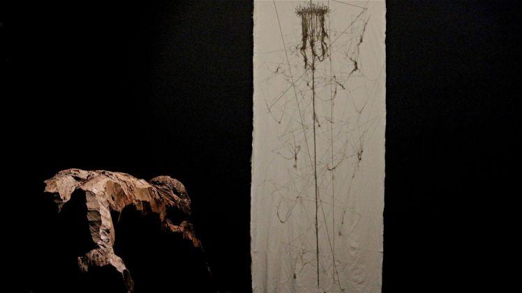 Maria Lai , Sindone, 1998. Stoffa, filo, cm 275 x 108; Pinuccio Sciola, Crocifisso, 1968. Legno di ulivo. Ph. Silvia Maglione Courtesy Archivio Maria Lai Musei Civici Cagliari
