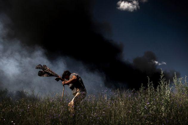 Valery Melnikov, Rossiya Segodnya, A woman escapes from a fire during an artillery attack in Krasnodon highway