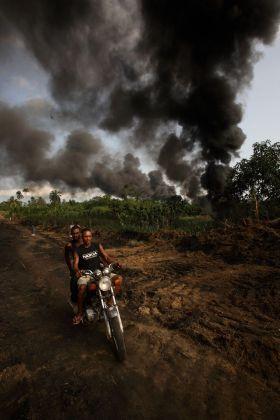 """George Osodi, Smoking Pipe, 2007 dalla serie """"Oil Rich Niger Delta"""" © l'artista, courtesy Fondazione Cassa di Risparmio di Modena"""