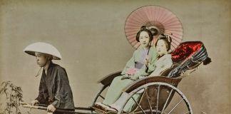 Giovani portatori di 'Kango' al lavoro. Gli uomini, in umili vesti, sono ritratti nell'atto di trasportare una giovane donna. 1863-1868 ca., stampa all'albumina dipinta a mano © Archivi Alinari, Firenze