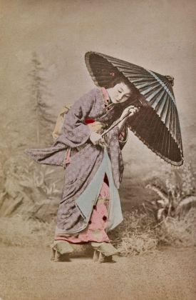 Una geisha cammina sfidando il vento con il suo ombrellino. 1870-1890, stampa all'albumina dipinta a mano, © Archivi Alinari, Firenze