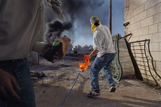 In una delle prime manifestazioni della seconda Intifada palestinese, i dimostranti lanciano pietre e molotov contro i soldati, che sparano munizioni vere e proiettili di gomma, a volte letali. Cisgiordania, Ramallah, 2000 © James Nachtwey/Contrasto