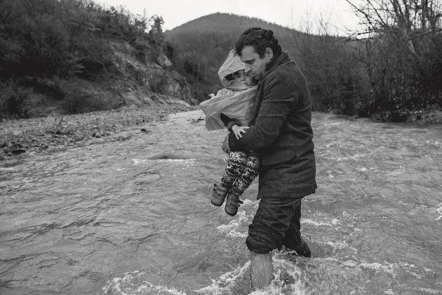 Un uomo porta in braccio il figlio mentre tenta di attraversare il confine con la Macedonia. Macedonia, 2016 © James Nachtwey/Contrasto