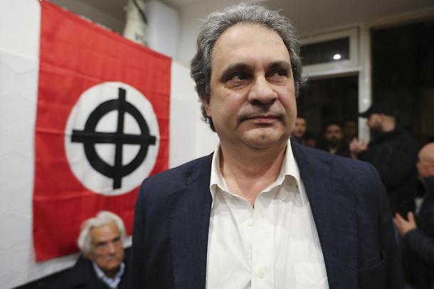 Roberto Fiore, leader di Forza Nuova, e alle sue spalle una bandiera con la croce celtica, simbolo diffuso in molti partiti neofascisti