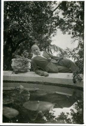 D'Annunzio semisdraiato a bordo fontana nei giardini del Vittoriale. Archivio Fondazione Vittoriale degli Italiani