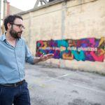 Il curatore Davide Ferri. Sullo sfondo il murale di Luca Bertolo nel cortile di EXATR, Forlì 2018. Photo Gianluca Camporesi