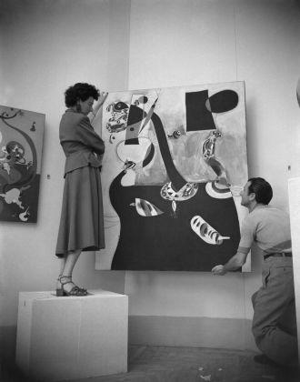 Peggy Guggenheim durante l'allestimento del padiglione greco con Interno olandese II (1928) e Donna seduta II (1939) di Joan Miró, XXIV Biennale di Venezia, 1948. Solomon R. Guggenheim Foundation, Venice, photo Archivio Cameraphoto Epoche