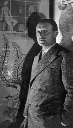 Un ritratto di Ponti davanti alla parete di un bar decorato a ceramiche Richard Ginori, progettato nel 1931 © Gio Ponti Archives