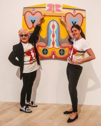 Judy Chicago e Maria Giulia Maramotti indossano la T-shirt in edizione speciale realizzata da Max Mara posando davanti al cofano d'auto da cui è tratta l'immagine riprodotta sulla maglietta