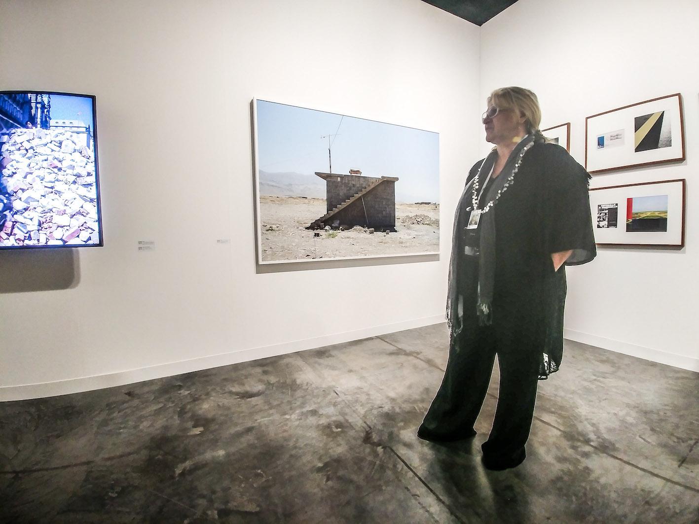 Ida Pisani della Prometeo Gallery con alle spalle opere di Beto Shwafaty e Hiwa K