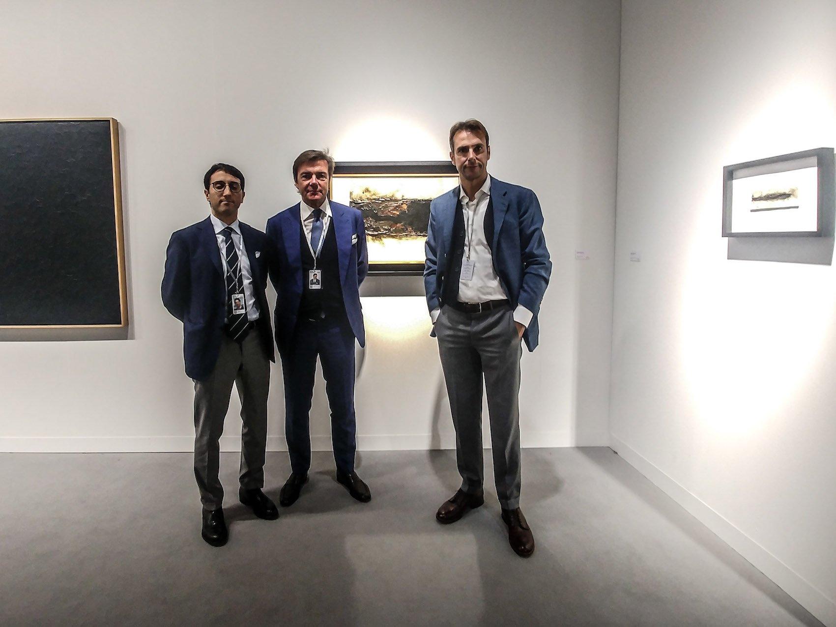 Da sinistra: Jose Graci, Davide e Luigi Mazzoleni con alle spalle Bianco Plastica B 2 di Alberto Burri