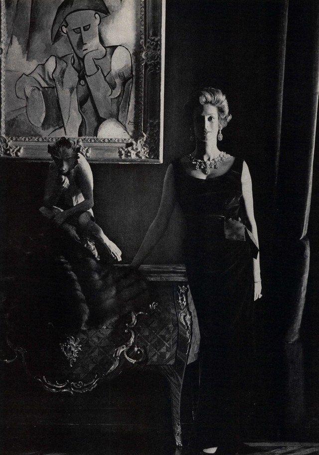 Marella Agnelli, wearing an emerald velvet dress by Dior, in front of a Picasso and an 18th c. sculpture of a monkey. Photo by Henry Clarke.