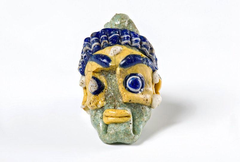 Pendente di collana in pasta vitrea che raffigura una testa maschile, prodotto da botteghe di area fenicio-cipriota