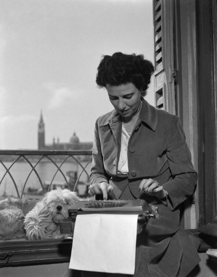 Peggy Guggenheim alla macchina da scrivere nella sua stanza all'Hotel Savoia & Jolanda, in Riva degli Schiavoni, Venezia, 1948. © Fondazione Solomon R. Guggenheim, foto Archivio CameraphotoEpoche, donazione Cassa di Risparmio di Venezia, 2005