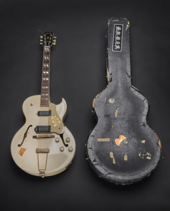 A 1950S GIBSON ES-295 with a white finish inside a hardshell contour case with orange plush lining. The guitar was used by Mick Jones during recording of the London Calling album and in the music video for the title track of the album, released as a single in December 1979. © The Clash