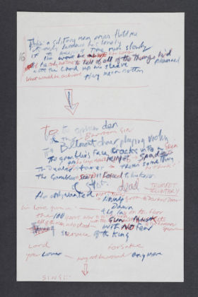 A set of working lyrics in Joe Strummer and Mick Jones' handwriting for the song The Card Cheat, 1979. The Card Cheat was released on the London Calling album in 1979. It features approximately 24 lines in blue pencil and red ink on white notepaper, with extensive additions and deletions as Strummer and Jones worked out the song's wording. © The Clash