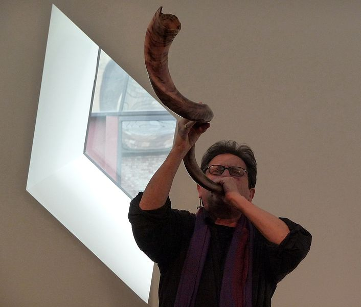 Alvin Curran playing a shofar next to window in performance at Contemporary Jewish Museum, San Francisco, on March 15, 2009. Photo by Susan Levenstein, fonte Wikimedia