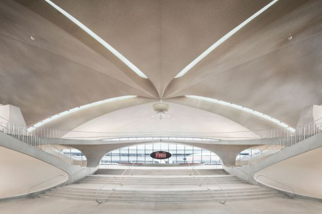 """A view toward The Sunken Lounge (and the hotel's 1958 Lockheed Constellation """"Connie"""") from the terminal's front entrance. Photo credits TWA Hotel – David Mitchell"""