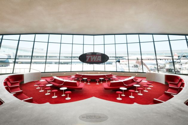 """The Sunken Lounge at the TWA Hotel boasts a split flap departures board by Solari di Udine — and a view of the hotel's restored 1958 Lockheed Constellation """"Connie"""". Photo credits TWA Hotel – David Mitchell"""