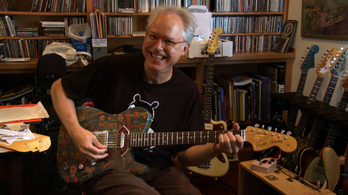 What is shown in the photograph: Bill Frisell laughing as he plays his guitar hand painted by friend Claude Utley Identify all people left to right: Bill Frisell Where was the image taken: In Bill Frisell's former home in Seattle. Frisell has since relocated to New York. When was the image taken: August 2011 Who took the photograph: Emma Franz Full credit line as it should appear: Photo courtesy of Emma Franz